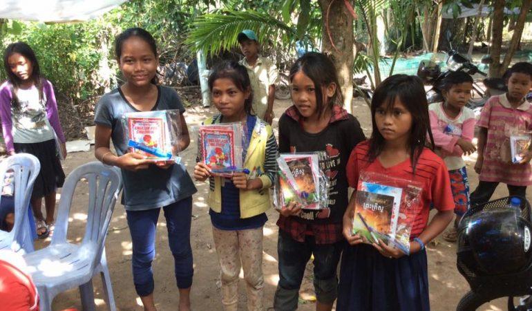Gruppi di bambini che hanno ricevuto del materiale scolastico e alcuni libri cristiani